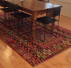 Colorful handmade vintage kilim rug under table
