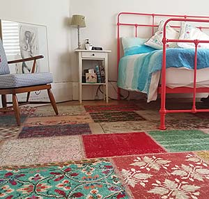 Colorful patchwork vintage rug in bedroom